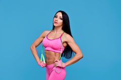 Sportive brunette girl in the pink sportswear with skipping rope Stock Images