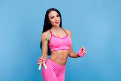 Sportive brunette girl in the pink sportswear with skipping rope Royalty Free Stock Photos