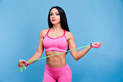 Sportive brunette girl in the pink sportswear with skipping rope Stock Image