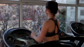 Sportive brunette running fast on treadmill, working hard to be healthy and fit stock video footage
