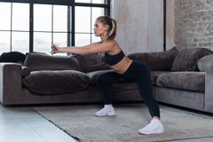 Sportive Caucasian female athlete in black sports bra and leggings doing side squat exercise at home.  royalty free stock images