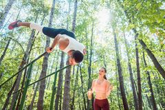 Sportive couple doing workout in outdoor gym Stock Images