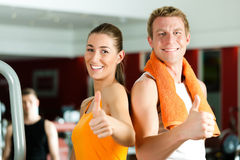 Sportive couple in gym. Or fitness club looking at the viewer Royalty Free Stock Photo