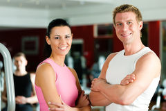 Sportive couple in gym. Or fitness club looking at the viewer Royalty Free Stock Images