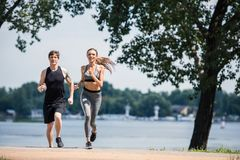Sportive couple jogging in park. Happy sportive couple jogging together in park Royalty Free Stock Images