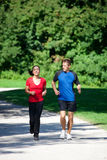 Sportive couple jogging together on summer day. Mature woman is jogging in her free time with her young personal trainer on a sunny and warm day Stock Photos