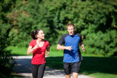 Sportive couple jogging together on summer day. Mature woman is jogging in her free time with her young personal trainer on a sunny and warm day Royalty Free Stock Photography