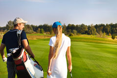 Sportive couple playing golf on a golf course walking to the nex Stock Image