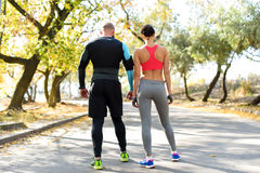 Sportive couple standing on road outdoors. Rear view of sportive couple standing on road outdoors Royalty Free Stock Photos