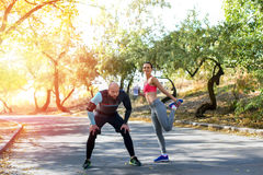 Sportive couple stretching on road outdoors. Front view of sportive couple stretching on road outdoors Stock Photos