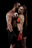 Sportive couple wearing boxing gloves and hugging isolated on black. Happy  sportive couple wearing boxing gloves and hugging isolated on black Stock Images