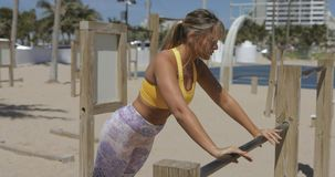Woman training on beach gym. Sportive curvy blonde in activewear training with bar in simple gym on sandy beach with city on background stock video footage