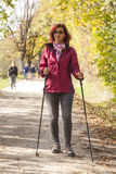 Sportive cute woman Nordic walking autumn cross country Royalty Free Stock Image