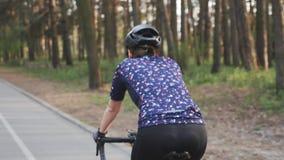 Sportive cyklista kobieta jedzie bicykl w parku Tylna strona pod??a strza? Kolarstwa poj?cie swobodny ruch zbiory
