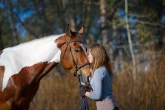 Sportive de fille et son cheval au printemps Image stock