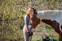 Sportive de fille et son cheval au printemps Images stock