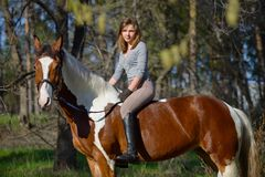 Sportive de fille et son cheval au printemps Image stock
