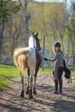 Sportive de fille et son cheval de nouveau aux écuries après la monte Images stock