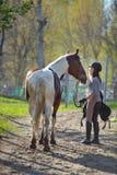 Sportive de fille et son cheval de nouveau aux écuries après la monte Photo libre de droits