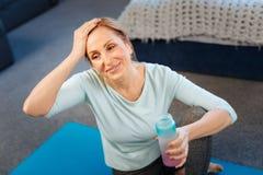 Sportive dysponowana dama jest męczący i naciera jej czoło zdjęcie stock