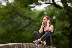 Sportive dziewczyna słucha muzyka w parku Zdjęcia Stock