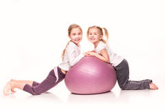 Sportive dziewczyny na dysponowanej piłce odizolowywającej nad bielem Zdjęcia Stock