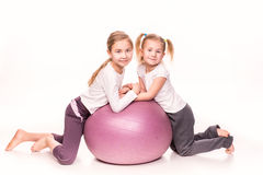 Sportive dziewczyny na dysponowanej piłce odizolowywającej nad bielem Obrazy Stock