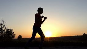 Small boy bends, dodges, and delivers a powerful uppercut at sunset in slo-mo. A Sportive Eleven-Year-Old Boy in Pants and a T-Shirt Bends and Delivers a stock footage