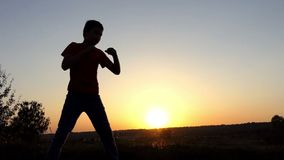 Small boy bends, protects his head, delivers a powerful uppercut at sunset in slo-mo. A Sportive Eleven-Year-Old Boy in Pants and a T-Shirt Protects His Head stock footage