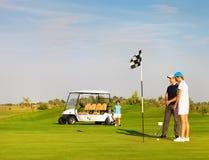 Sportive Familie, die Golf auf einem Golfplatz spielt Stockfotos