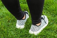 Sportive female training shoes. Close up sportive female training shoes on the green grass while doing fitness exercises Stock Photo