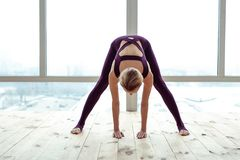 Sportive fit lady bending over on city background royalty free stock image