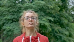 Sportive fitness girl in eyeglasses is warming out ready to exercise outside in the park during spring or summer morning. Under the rain. Healthy lifestyle stock video footage