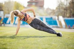 Sportive fitness woman is doing side plank on the stadium. Sportive woman is doing side plank on the stadium stock photos