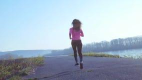 Sportive flicka som joggar längs flodbanken under soluppgång eller solnedgång det sunda livsstilbegreppet av den idrotts- kvinnan stock video