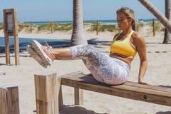 Sportive Frau, die auf Strand in der Turnhalle trainiert Lizenzfreies Stockbild