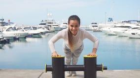 Sportive Frau, die crossfit Übung draußen tun durch den Ozeanpier ausbildet stock video footage
