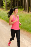 Sportive Frau, die durch Wald läuft Stockfotografie