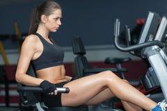 Sportive Frau, die exirsise auf Radfahrensimulator tut Lizenzfreies Stockbild