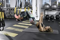 Sportive girl does exercise in gym. Athletic girl is training with TRX straps in the gym. She leans on her shoulders on the mat while her feet are in the straps Royalty Free Stock Images