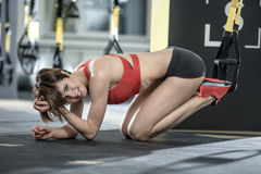 Sportive girl does exercise in gym. Joyful girl stands on the knees and elbows on the floor in the gym. Her feet are on the TRX straps. She wears red top and Royalty Free Stock Image
