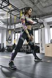 Sportive girl does exercise in gym Royalty Free Stock Images