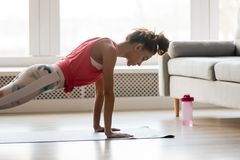 Sportive girl doing push press ups exercise at home. Young attractive sportive woman wearing activewear doing push ups or press ups exercise position on sport stock photo