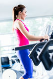 Sportive girl doing workout on treadmill Royalty Free Stock Photo