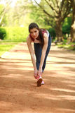 Sportive girl exercising outdoor in summer park before a run Royalty Free Stock Images
