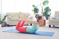 Sportive girl in fashionable tights doing bow pose Stock Photo