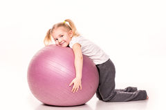 Sportive girl on a fit ball isolated over white Royalty Free Stock Photography