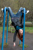 Sportive girl hanging on horizontal bar Royalty Free Stock Photography