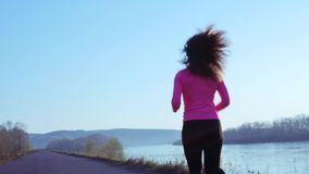 Sportive girl jogging along the river bank during sunrise or sunset. healthy lifestyle concept of athletic woman goes in. Sportive girl jogging along the river stock video