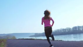 Sportive girl jogging along the river bank during sunrise or sunset. healthy lifestyle concept of athletic woman goes in. Sportive girl jogging along the river stock video footage